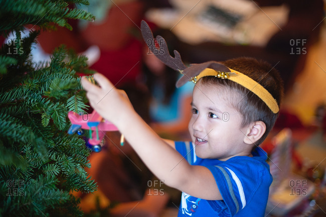 Little boy decorating a Christmas tree