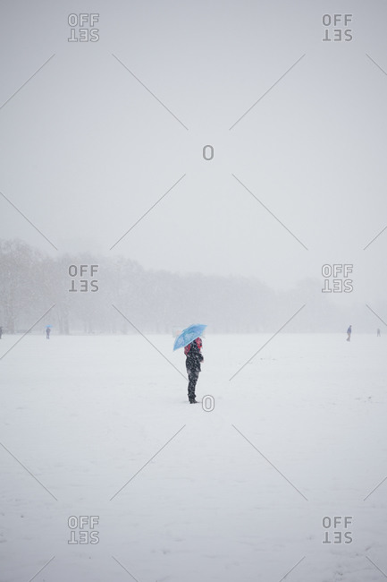 Woman with an umbrella in snow at Hyde Park in London