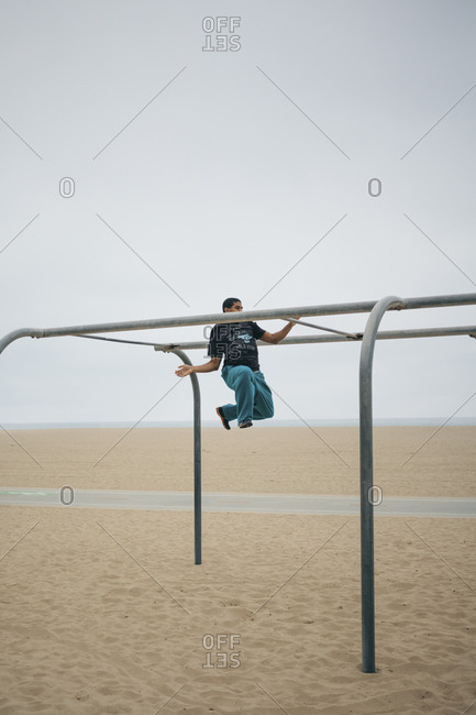 Santa Monica, California, USA - March 17, 2013: Man performing tricks on bars on the beach