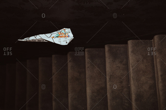 A paper plane flying over stairs