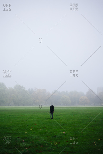 Woman standing in the middle of foggy Victoria Park in London