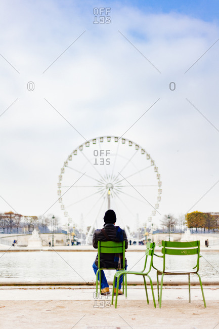 Man watching a ferris wheel on the Place de la Concorde in Paris
