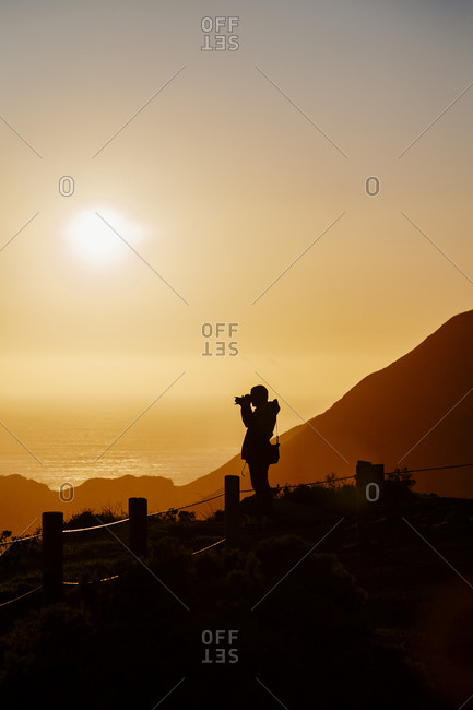 Man photographing at sunset near Golden Gate Bridge in San Francisco