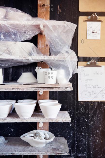 Shelves of unglazed pottery at a ceramist's studio