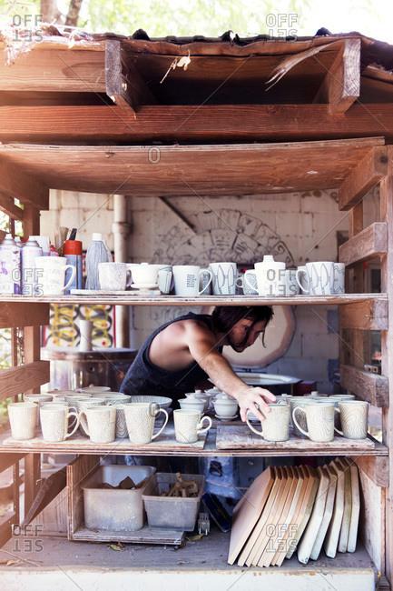 Ceramist placing finished mugs on a shelf