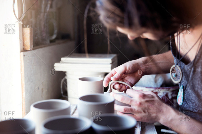 Ceramist attaching a handle to a mug