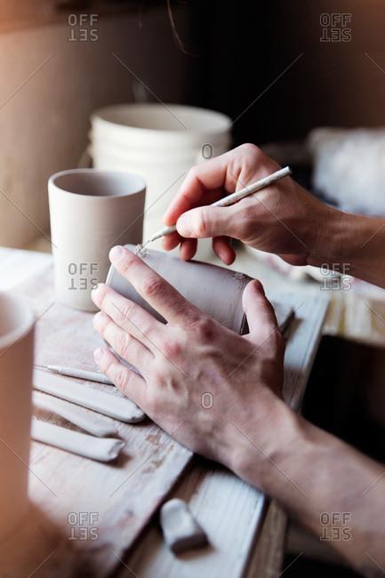 Ceramist etching an unfired clay mug