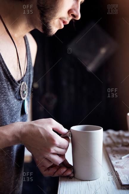 Ceramist adhering a handle onto a mug
