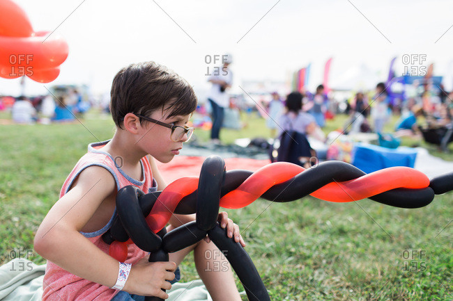 Boy at a festival playing with a gun shaped balloon
