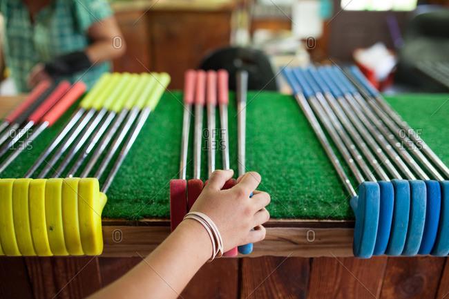 A girl picks out a club at a miniature golf course