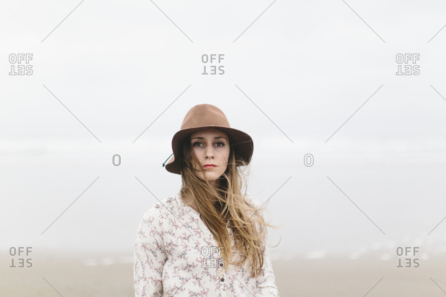 Portrait of woman in a hat on a windswept beach