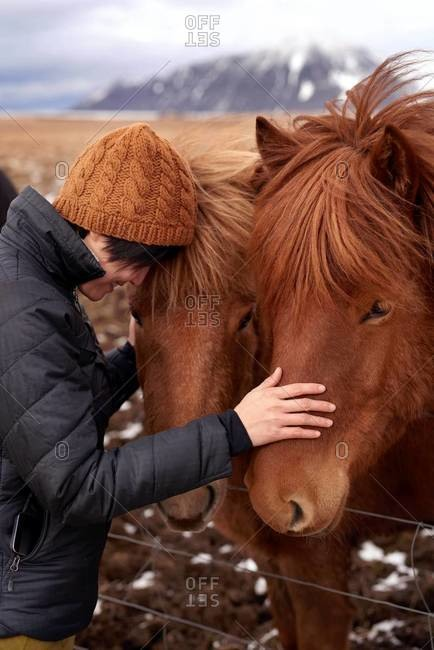 A woman petting Icelandic horse in rural Iceland