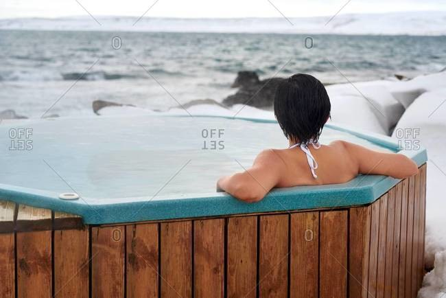 A woman in a hot tub by a geothermal pool in Drangsnes, Iceland