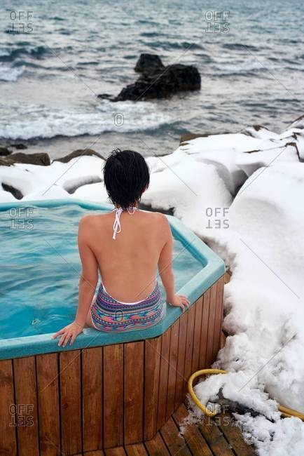 A woman in a wooden hot tub by a geothermal pool in Drangsnes, Iceland