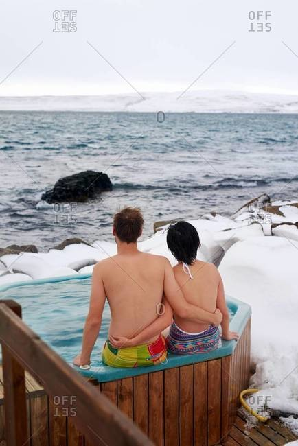 A couple in a wooden hot tub by a geothermal pool in Drangsnes, Iceland