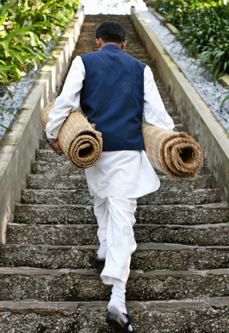 A man walking up stairs with yoga mats