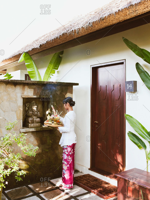 A woman making morning offerings at a luxury hotel in Bali, Indonesia