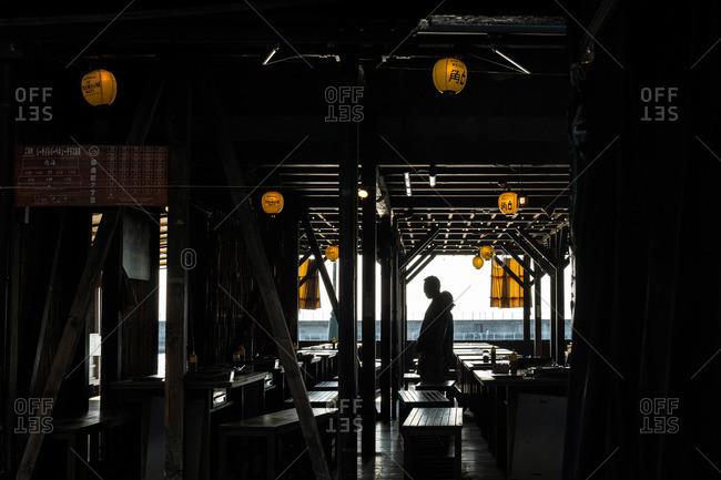 Kemi, Japan - July 18, 2015: Person walking through seating area of a waterside restaurant