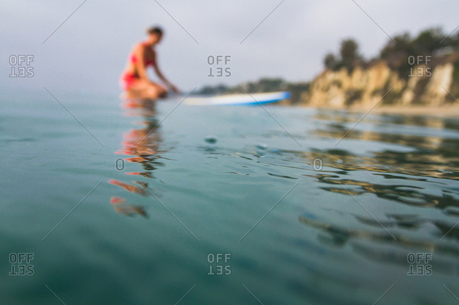 Woman practicing yoga on a paddleboard in the ocean