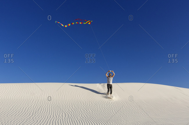 Flying a kite from dunes in White Sands, New Mexico