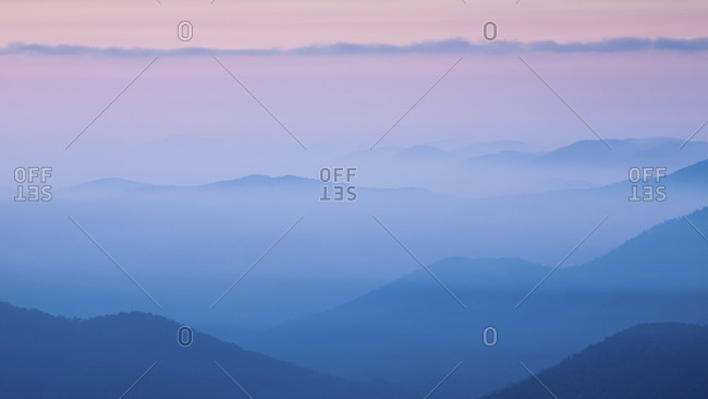 Misty blue mountains and purple sky