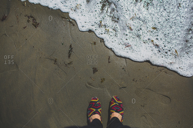 A woman in shoes at the beach