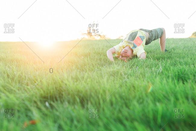 A boy attempts a backflip in a field