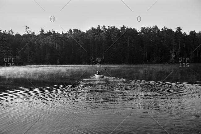 A boy kayaks through a lake