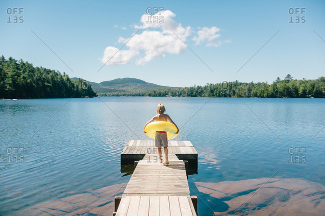 A boy with an inner tube walks towards a forest lake