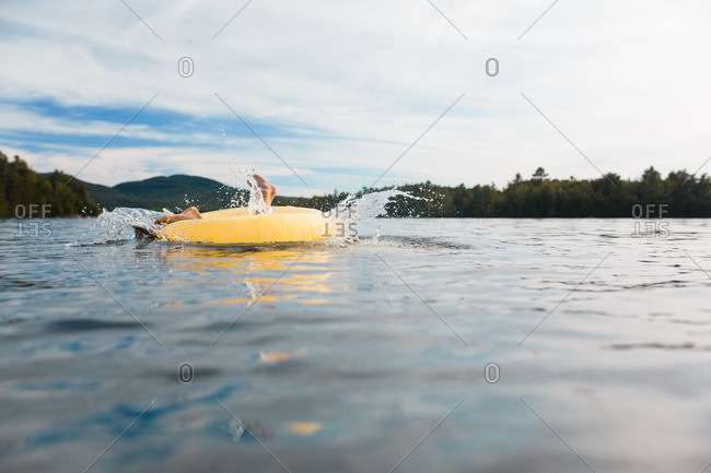 A boy falls through an inner tube in a forest lake