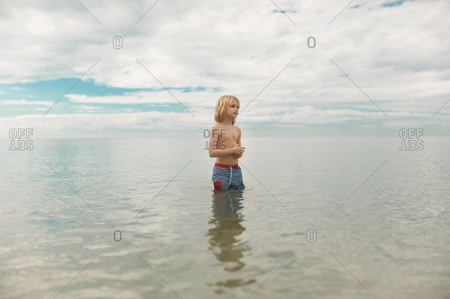 A boy pondering life in the ocean