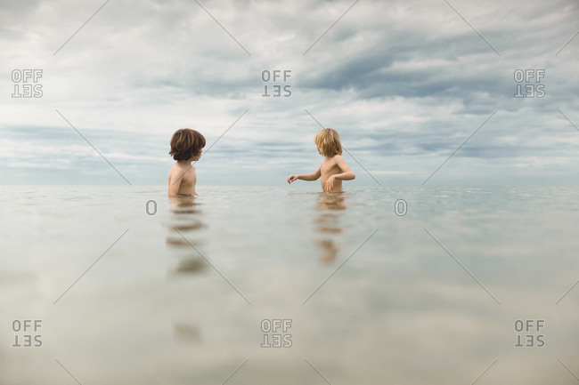 Two children wade in the ocean