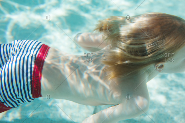 A boy swims by in a swimming pool
