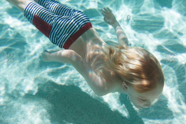 A boy swims near the floor of a pool