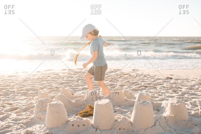A boy walks around a sandcastle