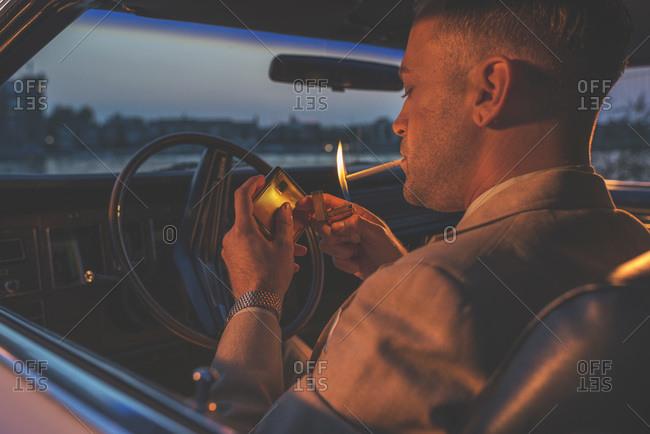 A man in a vintage car lighting a cigarette