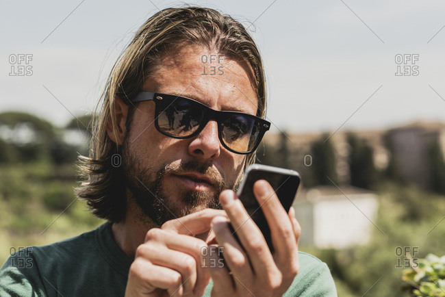 Man with long hair and sunglasses sending a text message
