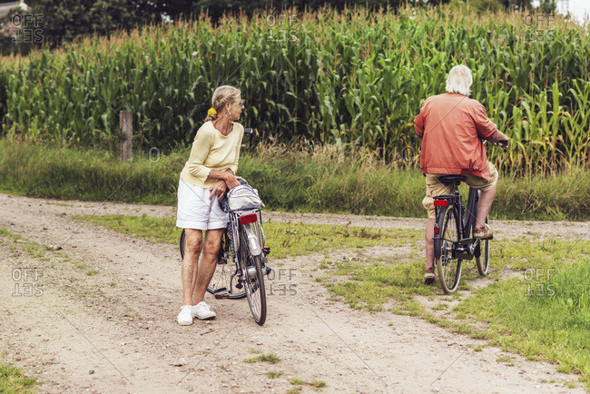 Retired senior couple with bikes near a corn field