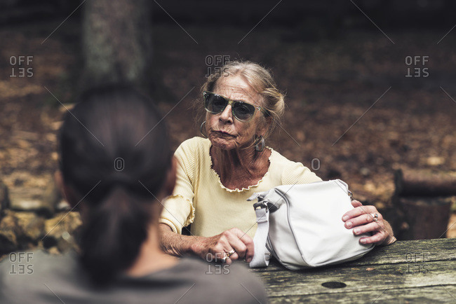 Senior woman having a conversation at a picnic table in a forest