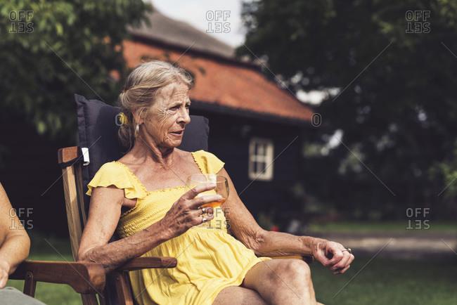 Senior woman enjoying a drink in a summer garden