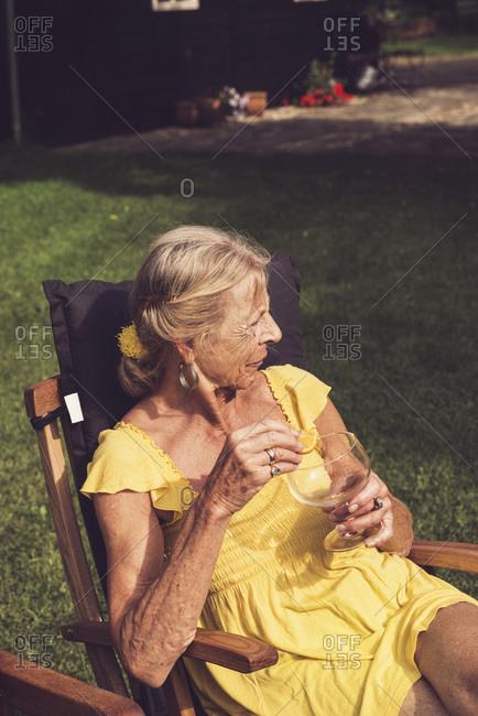 Senior woman enjoying a summer drink in a garden