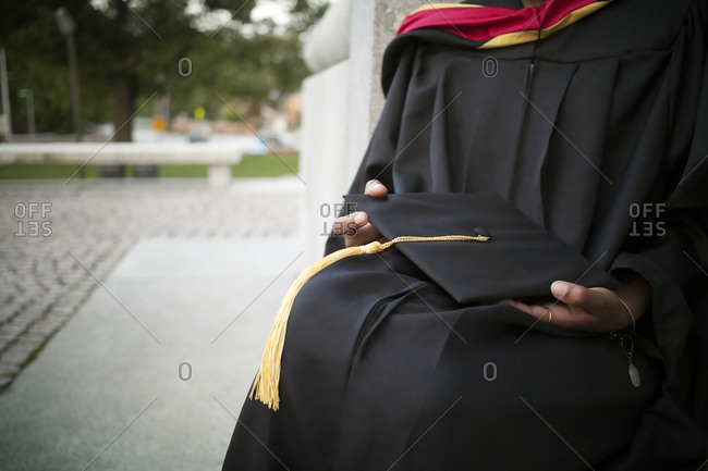 Woman in graduation gown sitting holding her cap