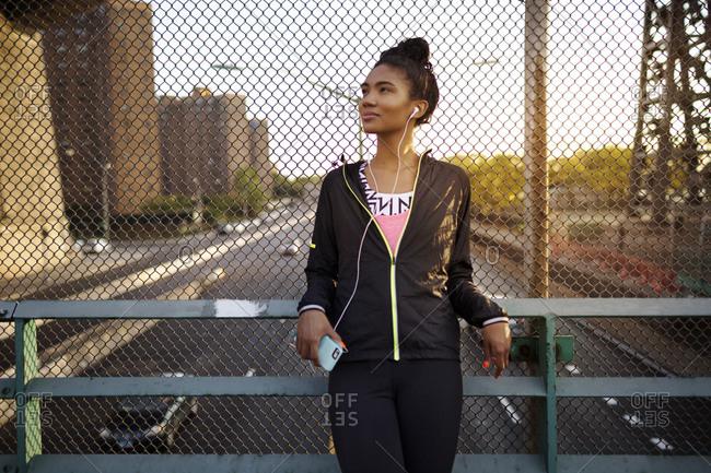 Female athlete listening to headphones on overpass