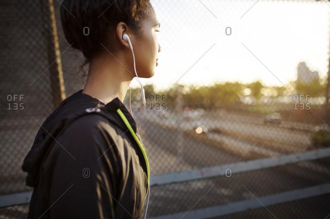 Female athlete listening to music on overpass
