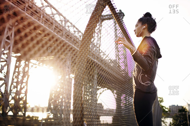 Woman in athletic clothes listening to music on bridge