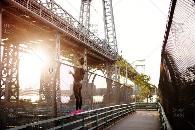 Woman balancing on railing of overpass