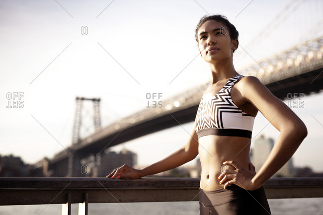 Female athlete by river gazing off with pride