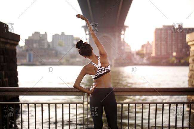 Female athlete under bridge stretching side