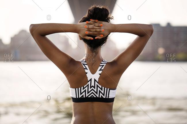 Female athlete under bridge stretching back