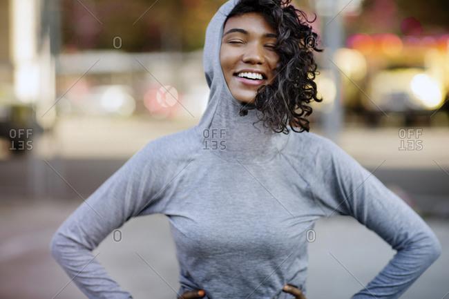 Woman in running hoodie smiling